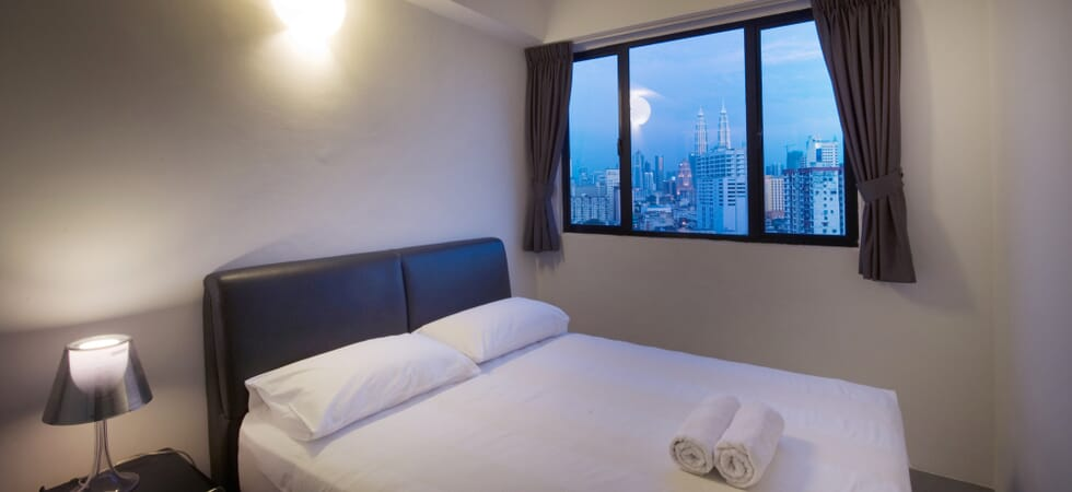 Second bedroom with queen-size bed and city view
